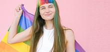 Queer person wearing a white top and coloured hair highlights holding the Pride flag