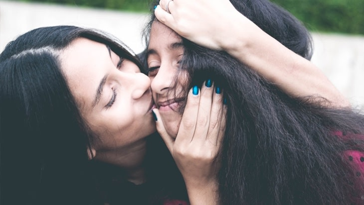 Mother kissing her teenager daughter on the cheeks
