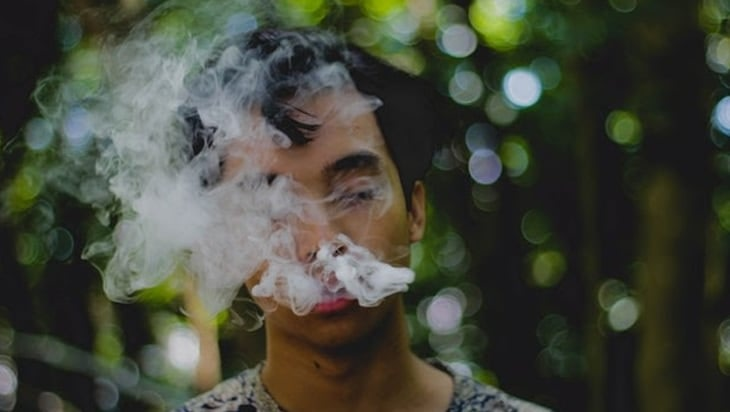 Queer person covered in smoke