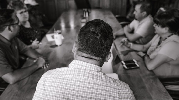 Grayscale photo of people in a meeting