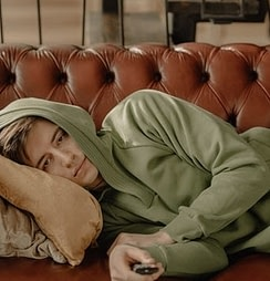 A guy wearing a green hoodie and denim jeans curled up in a brown couch holding a remote control