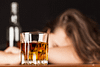 A woman passed out on a bar with a glass of alcohol in front of her