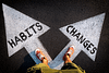 """Person standing on two arrows that read """"habits"""" and """"changes"""""""