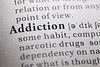 Close up of the dictionary definition of addiction