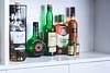 A variety of liquor bottles lined up on a shelf