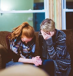 Two women holding hands and crying on a couch