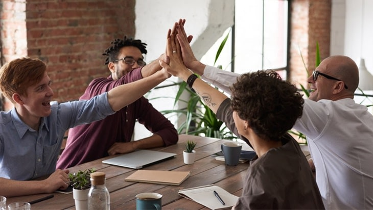 People doing a high-five at a meeting