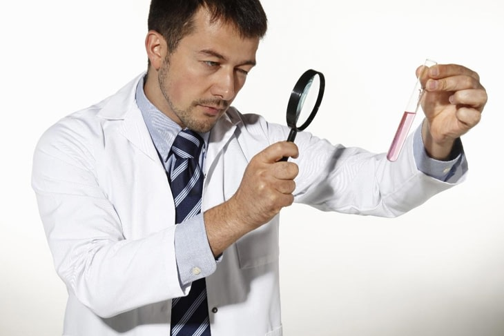Close up of a doctor looking at a chemical test tube