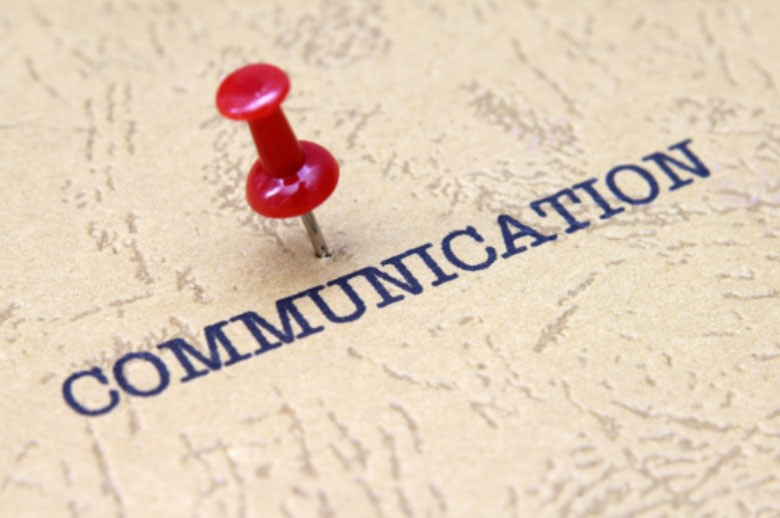 Close up of a bulletin board with the word 'communication' written on it